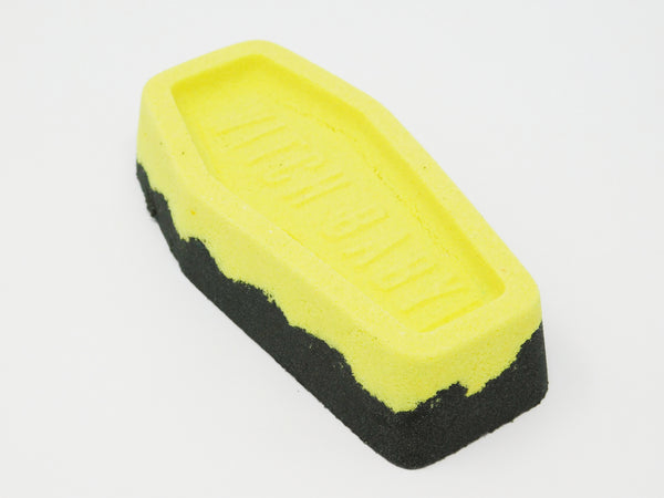 Black and yellow coffin shaped bath bomb. Bath bomb that turns your bath water dark red.