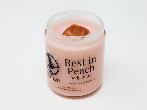 Peach colored body butter topped with Peach Moonstone. Body butter that smells like peach tea and tobacco. Body butter made of shea, sunflower oil, and coconut oil.