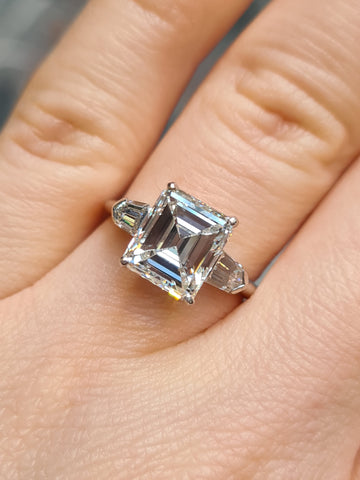 Emerald cut diamond ring with bullet cut shoulders