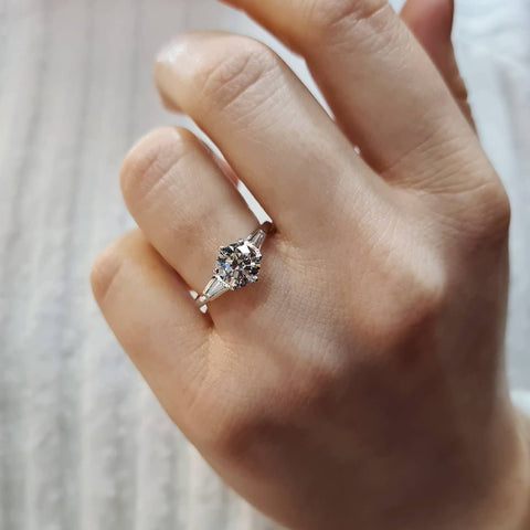 Round brilliant cut diamond ring with tapered baguette shoulders