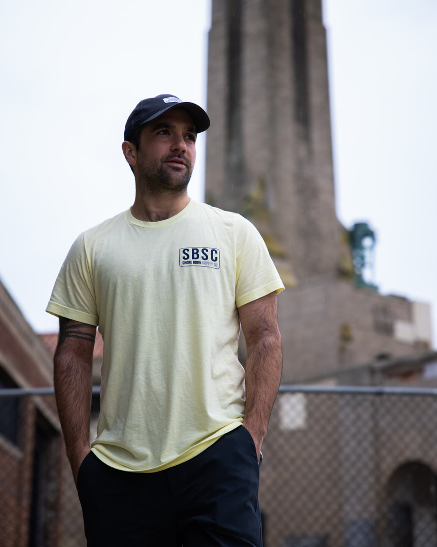 The Shore Born Logo T in washed yellow with navy ink