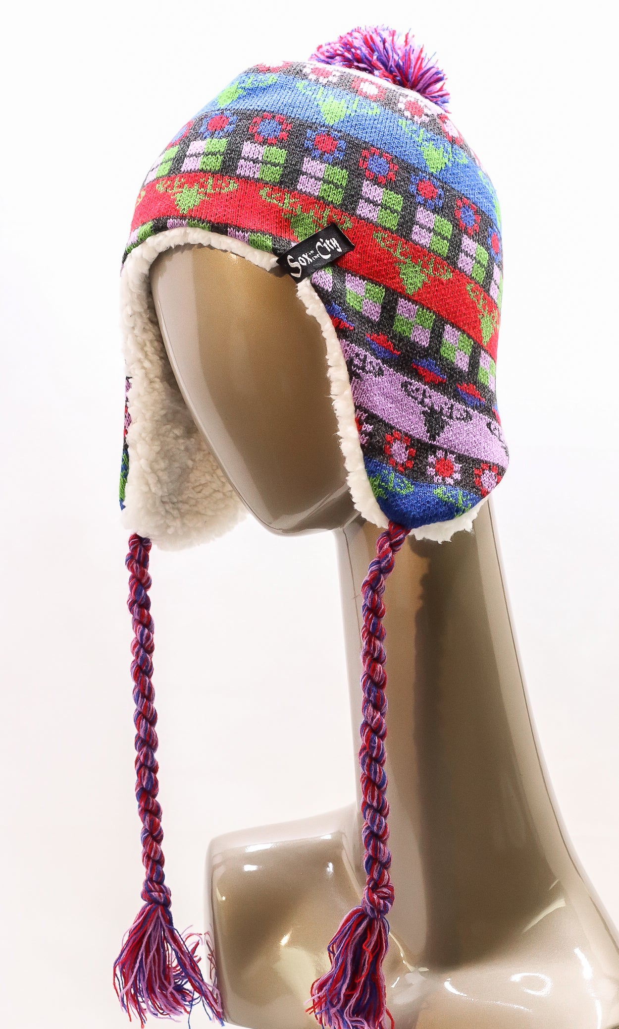 KNITTED MULTI-COLORED PLUSH-LINED EAR-FLAPS HAT WITH TASSELS AND POM-POM