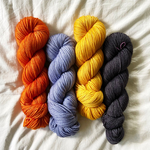 Spice Orange, Soft Blue, Golden Yellow, and Dark Gray lined up
