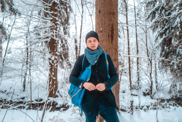 Young man with unisex triangular scarf in the snowy forest