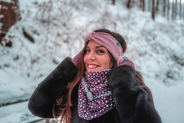 Woman with winter triangle scarf and headband in the snow