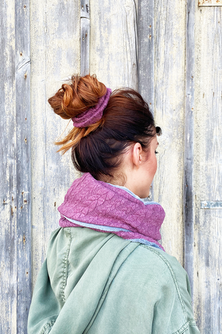 Young woman wearing messi bun hairstyle with scrunchie hair tie fake knit cable knit berry