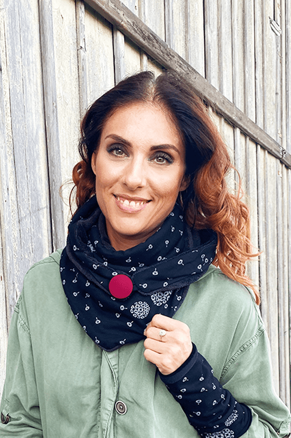 Woman with matching triangle scarf with red button and black arm warmers