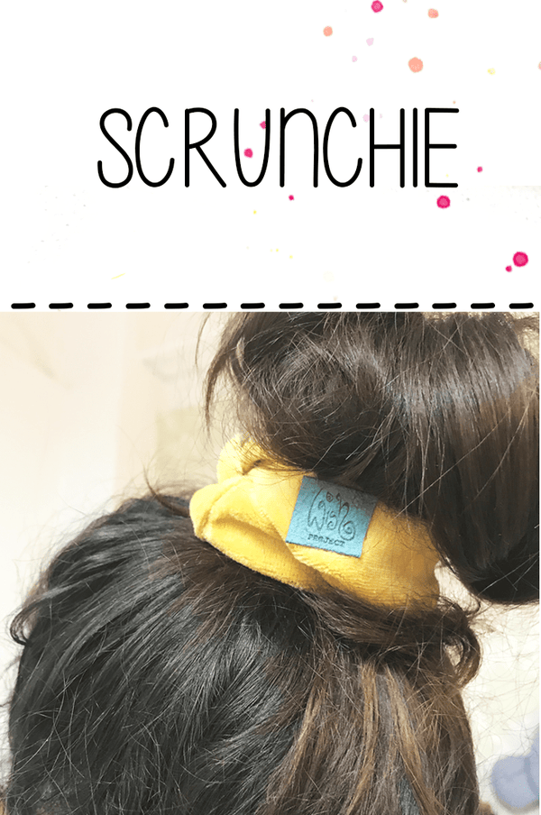 scrunchie hair gum made of gold-yellow cotton in the fireplace