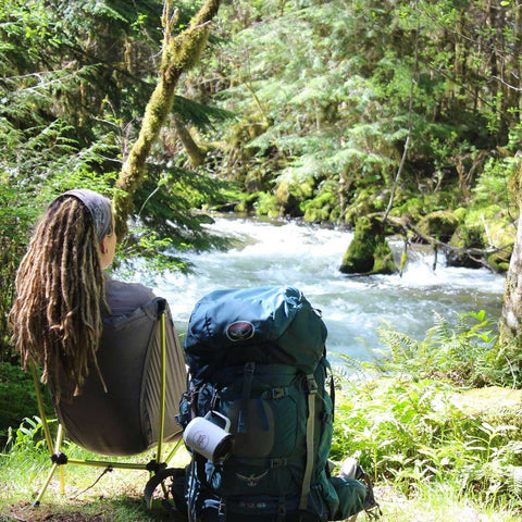 Susan camping by a mountain stream