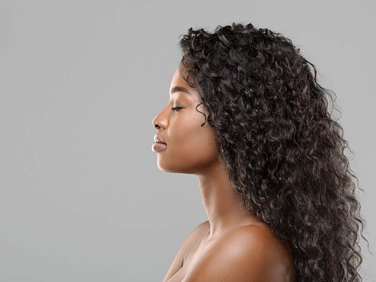 A beautiful curly african american woman wearing a wig.