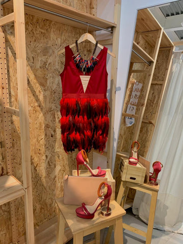 Red and black dress with feather accents with a black and hot pick chunky necklace and deep pink heels.