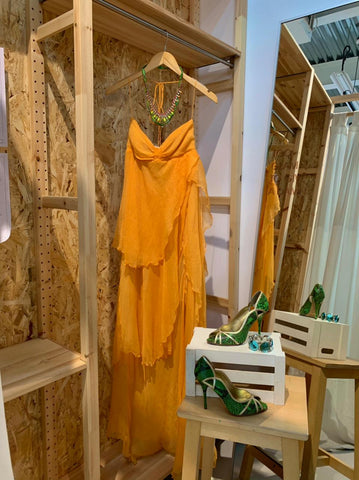 flowy orange dress with green and gold heels with a matching green and gold necklace.