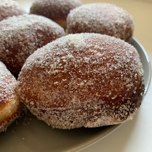 Brioche donuts sprinkled with cinnamon and sugar.
