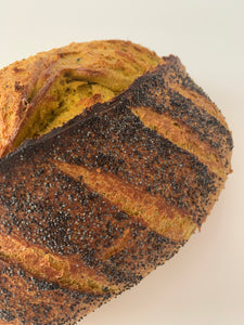 Turmeric loaf of bread with poppy seeds sprinkled on top.