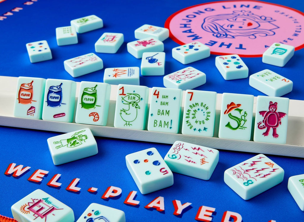 American Mahjong Tile set called the Cheeky demonstrated on a blue playing mat and set on pushers