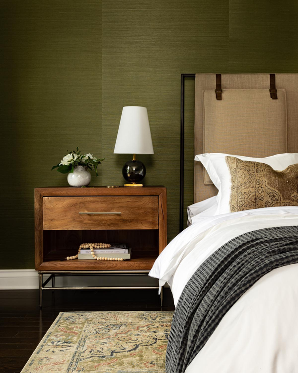 close up bedroom with grasscloth green wallpaper.