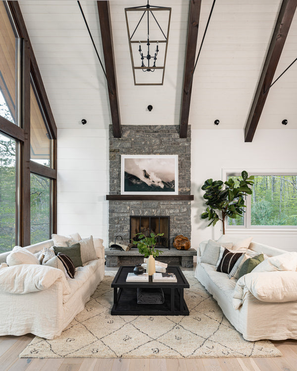 Living room with high ceilings and stone fireplace.