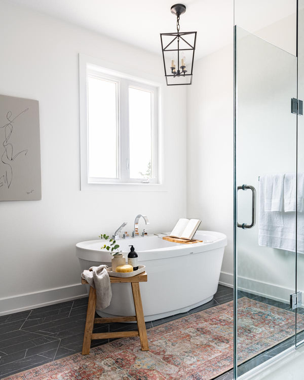 Bathroom with patterned floors and runner.