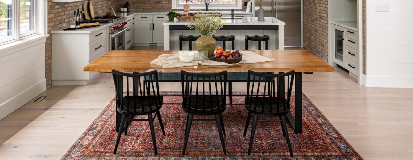 Wooden dining table with black chairs and rug.