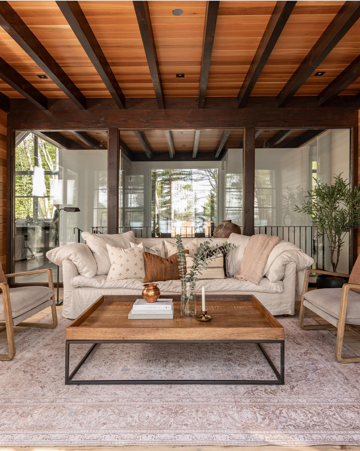 Wood paneling sunroom with couch and chairs.