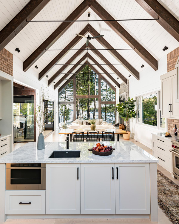 open concept kitchen with big window and wood beams on ceiling.