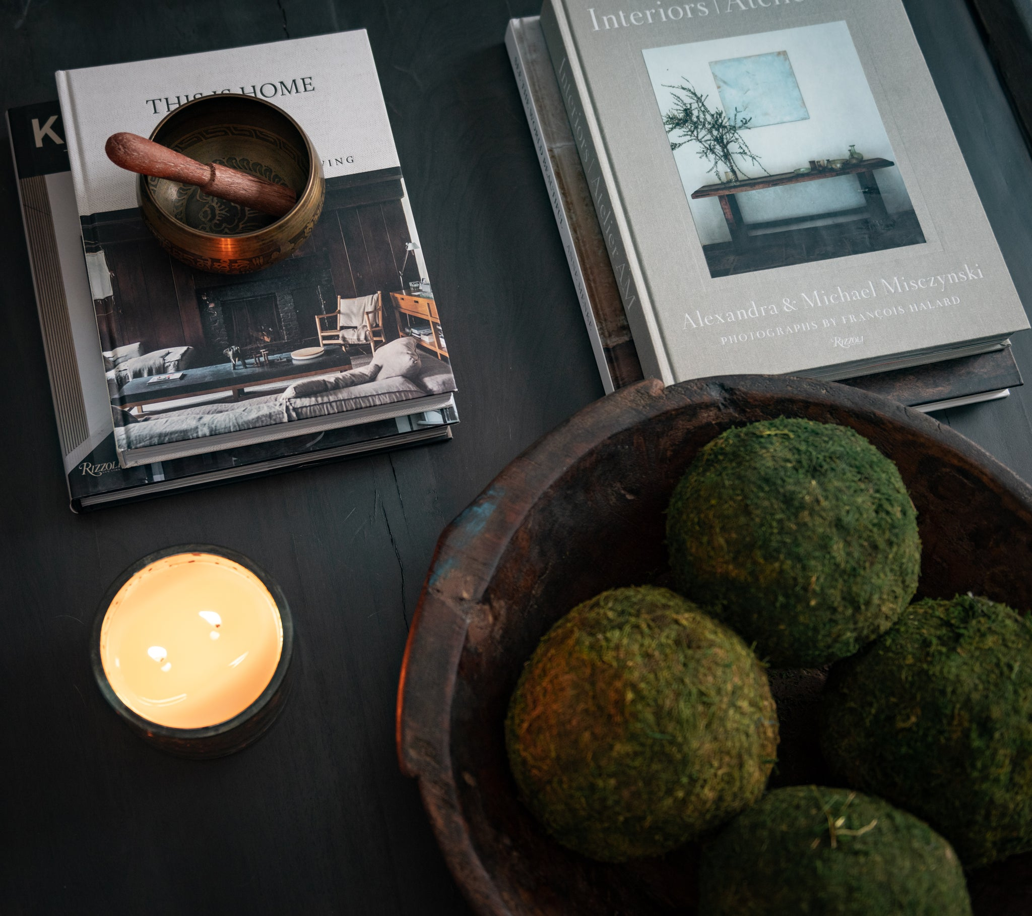 Crossing Bridge zoom in on coffee table. Books, singing bowl, candle.