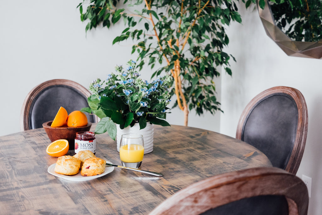 Kitchen table with glass of orange juice, scones, and floral arrangement.