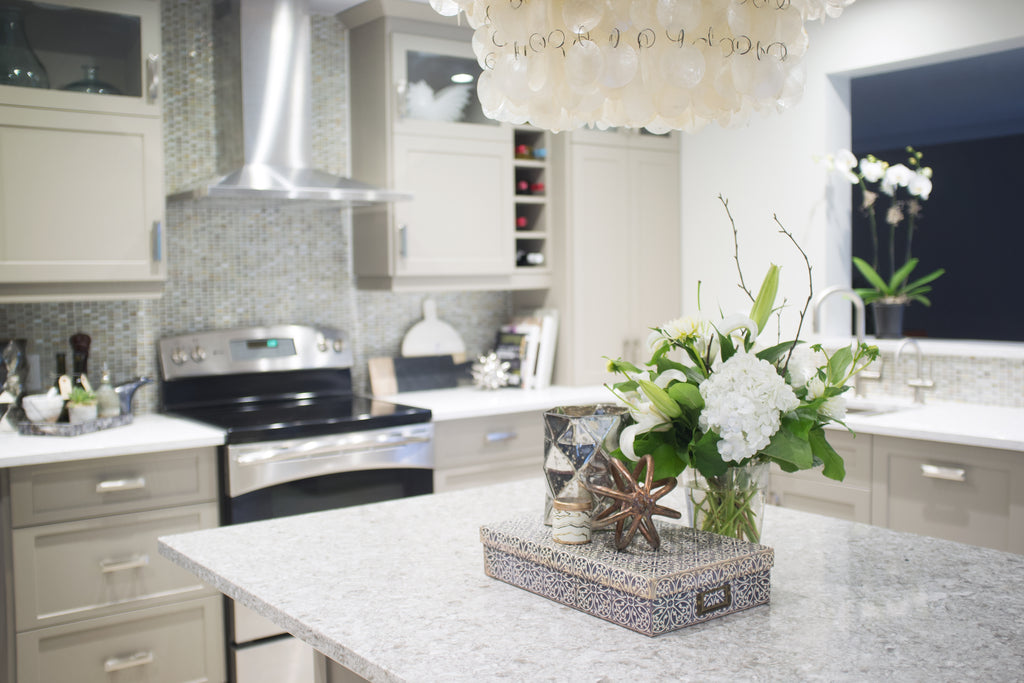 Kitchen with island, box, flowers and chandelier.