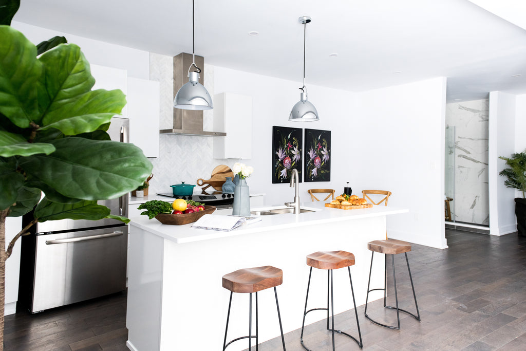 White commercial kitchen with wooden stools.