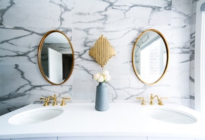 White marble vanity with grey veining and brass elements