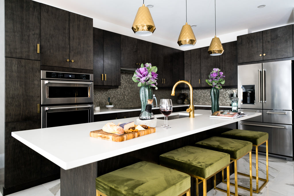 Kitchen with island, green and gold stools, cheese, wine and vase.