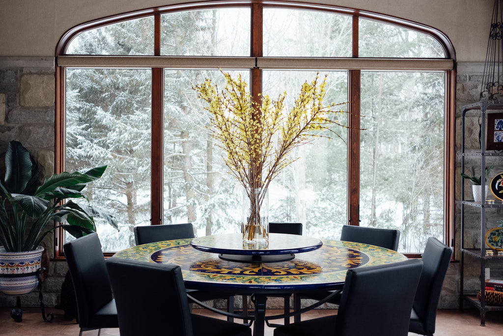 Round dining room table with glass vase and branches.