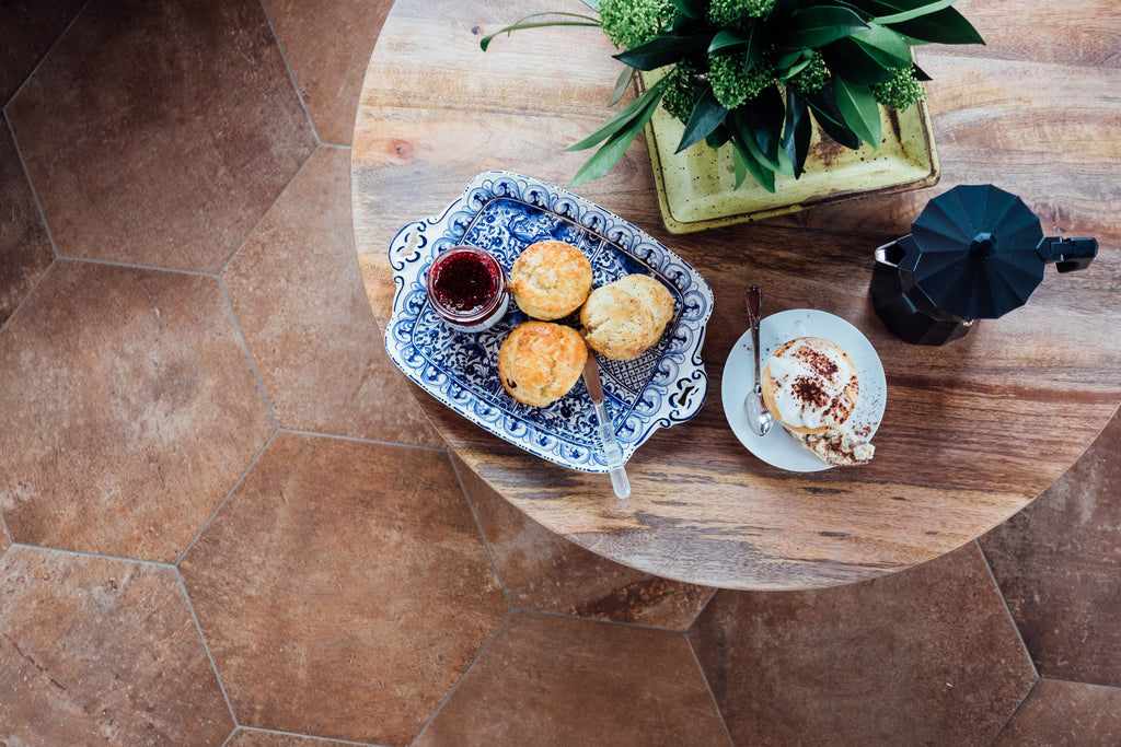 Flat lay view of coffee table with scones, cappuccino, and flowers.