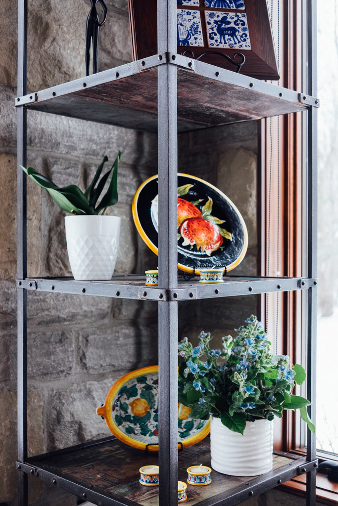 Metal framed display shelf with ceramic plates and vases.