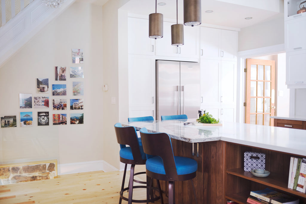 Kitchen counter with stools beside a wall with photos
