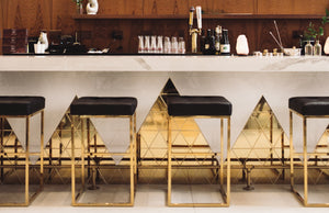 Cocktail bar with brass finishes and leather barstools