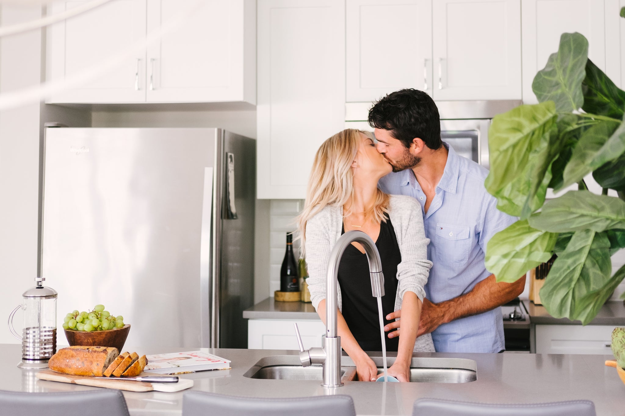 Couple kissing in the kitchen.