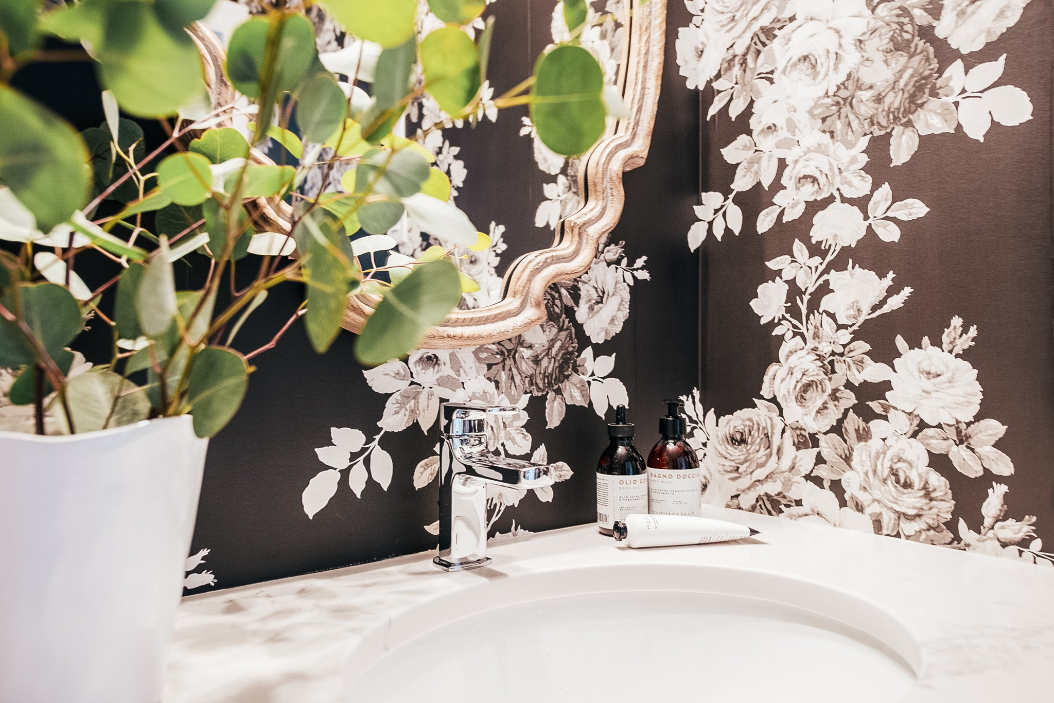 Rosewood condo bathroom sink and floral wallpaper.