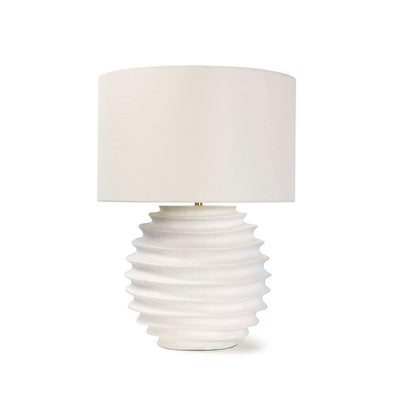 White table lamp with linen shade and accordion-like fluting on round base.