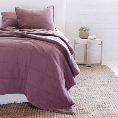 The Fira Bedding Collection in berry is 100% cotton, has a large quilted pattern, and is available in a variety of sizes.