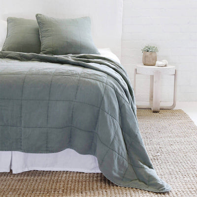 The Fira Bedding Collection in moss is 100% cotton, has a large quilted pattern, and is available in a variety of sizes.