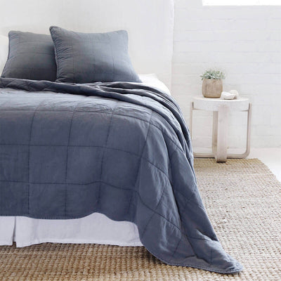 The Fira Bedding Collection in navy is 100% cotton, has a large quilted pattern, and is available in a variety of sizes.