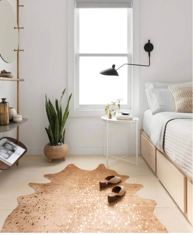 Gold and tan cowhide rug in a bedroom.