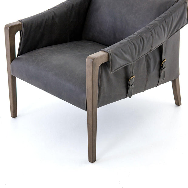 Modern living room chair with buckle details and birch wood frame.