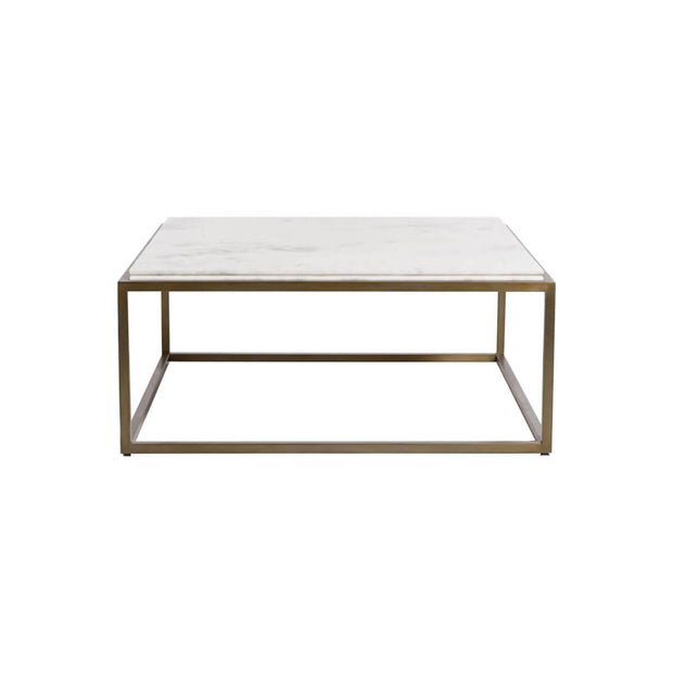 The Himara Coffee Table has a antique brass metal frame and a thick, white marble top.