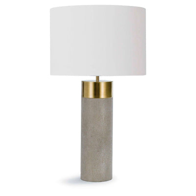 The Belo Table Lamp features a fabric shade atop a brushed brass column base.