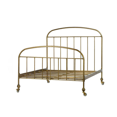 Bed with a traditional iron bed frame on casters in an antique brass finish.