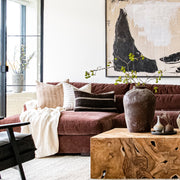 Rustic, bohemian living room featuring a knotted wood coffee table and burgundy sofa, decorated with textural, striped throw pillows.