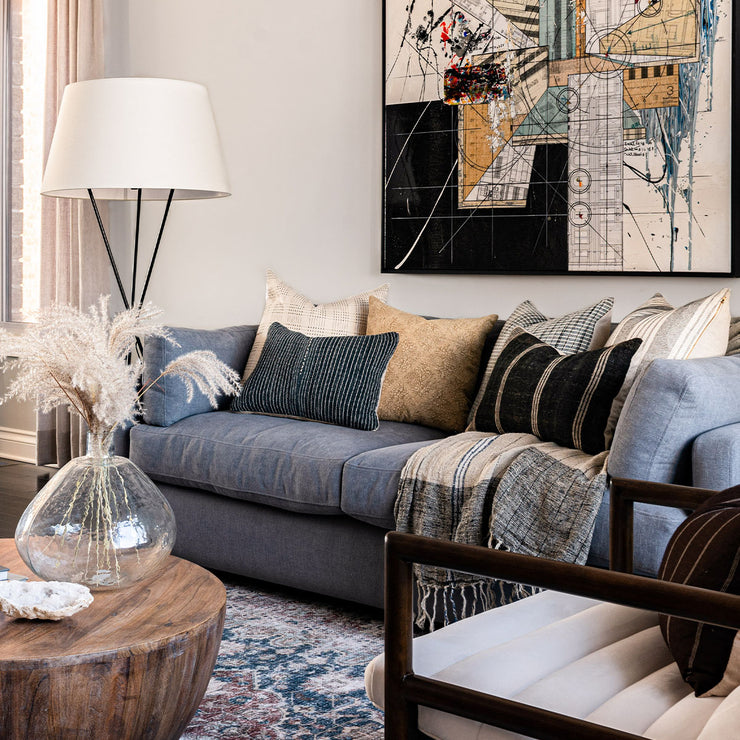 Blue-toned modern living room with antique rug, grey sofa, and throw pillows.