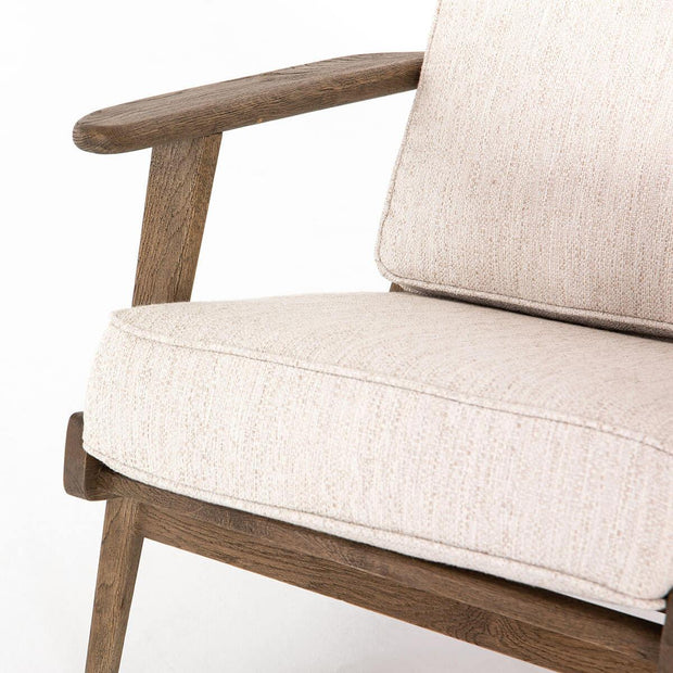 Closeup of the modern lounge chair with neutral cushions and solid wood frame.